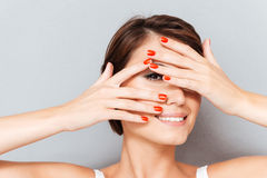 Close up portrait of a woman looking through fingers Stock Photography