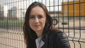 Close up portrait of woman near fence mesh. The woman standing at the mesh fence near the Playground and looking at the camera stock footage