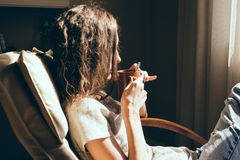 Close up portrait woman relaxing in comfortable modern chair near window in livingroom drinking tea. Warm natural light. Cozy home Stock Images