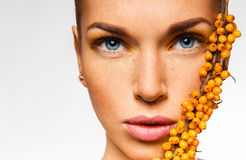 Close up portrait of woman with sea buckthorn Royalty Free Stock Photo