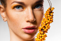 Close up portrait of woman and sea buckthorn Royalty Free Stock Photography