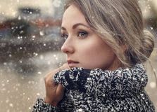 Close up portrait of woman with snow falling. Close up portrait of beautiful young woman in warm knitted sweater outdoors with snow falling Stock Photography