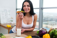 Close-up portrait of woman standing in kitchen, leaning on wooden table, having snack. Smiling girl maintains healthy Royalty Free Stock Photography
