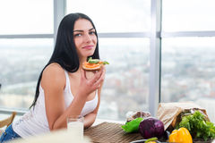 Close-up portrait of woman standing in kitchen, leaning on wooden table, having snack. Smiling girl maintains healthy Royalty Free Stock Photo