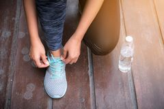 Close-up portrait of woman tying her shoes preparing for outdoor Royalty Free Stock Photos