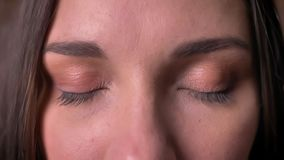 Close-up portrait of a woman, who watches into the camera and closes her eyes. stock footage