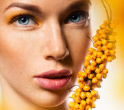 Close up portrait of woman and yellow sea buckthorn Royalty Free Stock Photos
