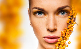 Close up portrait of woman with yellow sea buckthorn Royalty Free Stock Photography