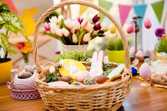 Close up portrait of wooden basket with easter composition, sweets, choco, gingerbread standing on table over decorative stock images