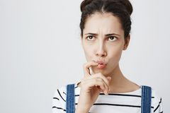 Close-up portrait of worried young european female, frowning and folding lips while thinking about something, looking up stock images