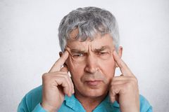 Close up portrait of wrinkled grey haired mature man keeps fingers on temples tries to find solution in mind or remember something. Wears formal clothing Stock Image