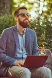 Close-up portrait of a writer with a full beard and stylish haircut, working with a laptop computer while sitting on a. Bench in a park royalty free stock photography