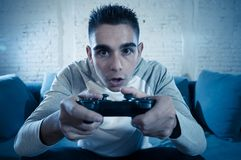 Close up portrait of young addicted man playing video game at night in gaming and addiction concept. Portrait of young student man playing video games at night royalty free stock image
