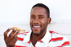 Young african man eating pizza stock photo