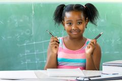 Little african girl sitting at desk in classroom with blackboard stock photo