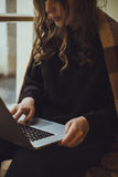 Close up portrait of a young american woman working on laptop an Royalty Free Stock Photo