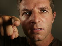 Close up portrait of young angry and upset man pointing with finger as if scolding and blaming you in rage feeling rageful showing. Intense mad and displeased Stock Photos