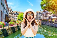 Close up portrait young asian woman looking excited holding her mouth opened amazing traditional colorful houses in La Petite Fran. Ce, Strasbourg, Alsace Royalty Free Stock Images