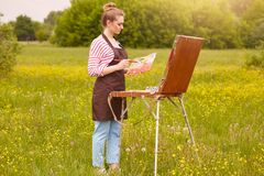 Close up portrait of young attractive artist in open air, being good at oil painting. Cute lady drawing landscape, likes to stock images