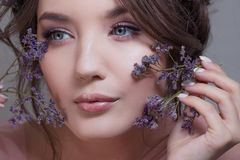 Close-up portrait of a young attractive and beautiful brunette. Fresh spring look with flowers. Skin care and freshness stock photos