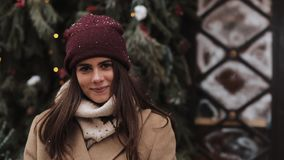 Close up portrait of young attractive brunette girl wearing winter hat and scarf looking to camera and smiling. Woman stock footage