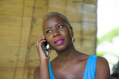 Close up portrait of young attractive and classy black afro american business woman in trendy and stylish hair talking on mobile p. Hone relaxed and thoughtful stock image
