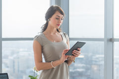 Close-up portrait of a young attractive freelancer using tablet for telework, typing and reading new messages on-line. Close-up portrait of a young attractive Royalty Free Stock Photo