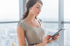 Close-up portrait of a young attractive freelancer using tablet for telework, typing and reading new messages on-line. Royalty Free Stock Photography