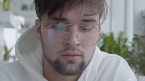 Close up portrait young attractive guy in glasses sitting in hub or restaurant and wotking on the laptop. Close up portrait of young attractive guy in glasses stock video