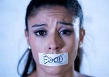 Close up portrait of young attractive latin woman with mouth sealed on stick tape with text no food in diet Anorexia eating royalty free stock images