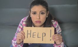Close up portrait of young attractive and sad hispanic woman sitting at home couch looking stressed and worried showing help sign. Feeling helpless in domestic Royalty Free Stock Photography
