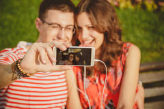 Close up portrait of young attractive tourist couple using a smartphone to take selfie on holiday. stock image