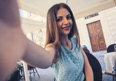 Close up portrait of a young attractive woman holding a smartphone digital camera with her hands and taking a selfie Royalty Free Stock Photography