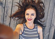 Close up portrait of a young attractive woman holding a smartphone digital camera with her hands and taking a selfie Royalty Free Stock Image