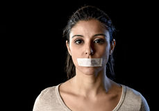 Close up portrait of young attractive woman with mouth and lips sealed in adhesive tape restrained. And abused censored and banned to speak and express opinion Stock Images