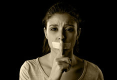 Close up portrait of young attractive woman with mouth and lips sealed in adhesive tape restrained. And abused censored and banned to speak and express opinion royalty free stock images