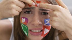 Close-up portrait of young attractive woman with painted social media icons on her face looking at camera touching her stock video
