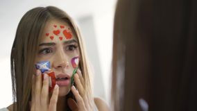 Close-up portrait of young attractive woman with painted social media icons on her face looking in the mirror with
