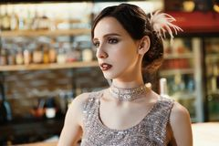 Close-up portrait of a young attractive woman in a 1920s style at the bar. Model with a beautiful make-up. In Bar stock photo