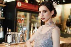 Close-up portrait of a young attractive woman in a 1920s style at the bar. Model with a beautiful make-up. In Bar stock images