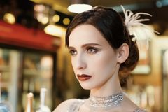 Close-up portrait of a young attractive woman in a 1920s style at the bar. Model with a beautiful make-up. In Bar royalty free stock photo