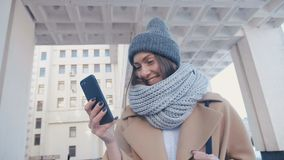 Close-up portrait of young attractive woman in stylish outfit Checks Smartphone outdoor at city background. Close up portrait of young attractive woman in stock footage