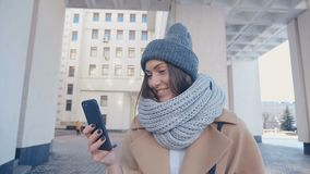Close-up portrait of young attractive woman in stylish outfit Checks Smartphone outdoor at city background. Close up portrait of young attractive woman in stock video footage