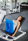Close-up portrait of young attractive woman training on simulator in gym Stock Images