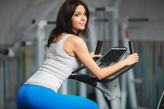 Close-up portrait of young attractive woman training on simulator in gym Royalty Free Stock Images