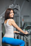 Close-up portrait of young attractive woman training on simulator in gym Royalty Free Stock Photo