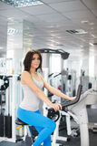 Close-up portrait of young attractive woman training on simulator in gym Stock Photography