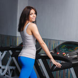 Close-up portrait of young attractive woman training on simulator in gym Royalty Free Stock Photos
