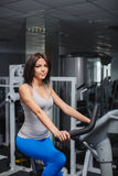 Close-up portrait of young attractive woman training on simulator in gym Stock Photo