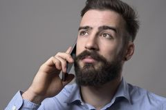 Close up portrait of young bearded business man talking on the mobile phone looking up at copyspace. Against gray studio background Stock Image